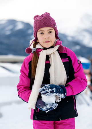 Portrait of cute girl playing in snowballs on top of high mountain photo