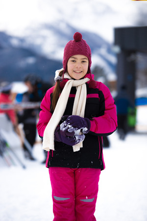 Beautiful smiling girl in pink ski suit posing against high mountain covered by snow photo
