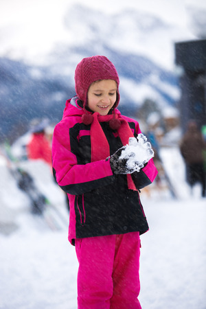 Beautiful smiling girl posing against high mountains with snowball photo