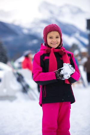 Beautiful smiling girl in pink ski suit making snowball photo