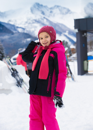 Cute smiling girl throwing snowball at highland resort photo