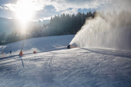 Landscape of snow cannons working on ski slope in Alps at sunny day photo