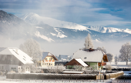 Beautiful landscape of traditional Austrian town in mountains covered by snow photo