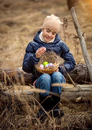 log basket: Happy smiling girl sitting on tree log at forest with Easter basket