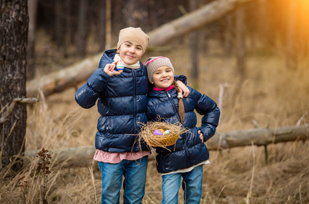 Two smiling girls posing with basket full of Easter eggs at forest photo