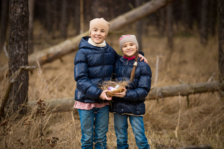 Closeup photo of two happy girls holding basket full of Easter eggs photo