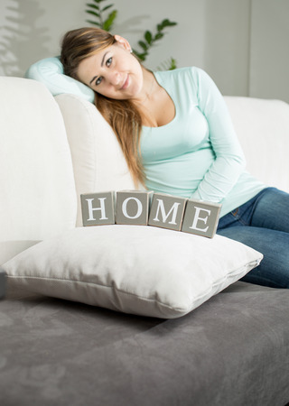 Closeup photo of young woman sitting on sofa and looking on word Home spelled by wooden cubes photo