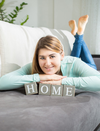 spelled: Beautiful smiling woman posing with word home spelled by letters on bricks Stock Photo