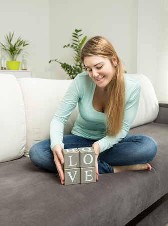 sense of space: Beautiful woman holding wooden bricks with letters making word Love