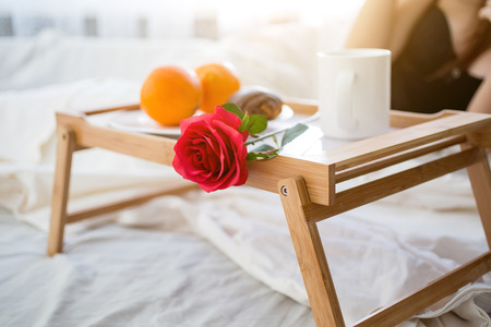 Closeup photo of tray with breakfast and red rose on bed at hotel room photo