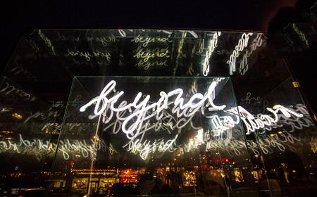 exceeding: Closeup photo of illuminated word beyond on street Stock Photo