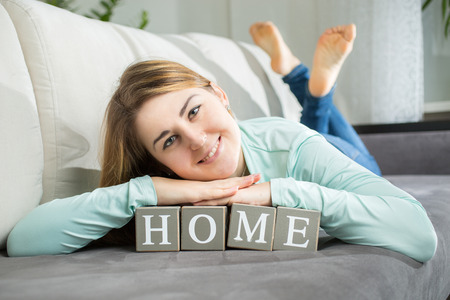 Closeup portrait of smiling woman lying on word home spelled by letters on bricks photo