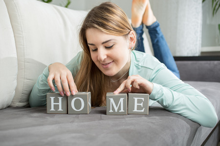 Portrait of cute woman making word Home from letters on bricks photo