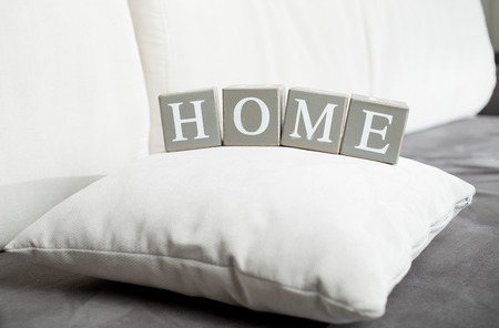 spelled: Closeup photo of word Home spelled on wooden blocks lying on sofa Stock Photo