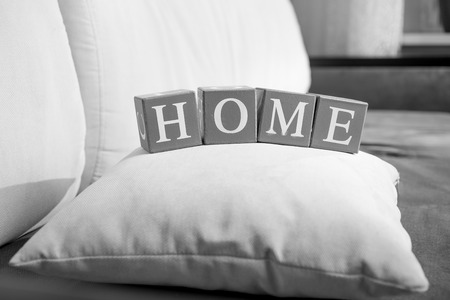 common room: Closeup black and white photo of word home spelled on wooden cubes Stock Photo