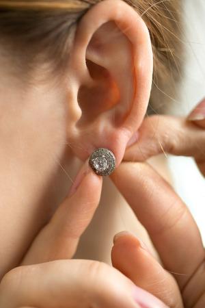 Macro photo of young woman trying on diamond earring photo