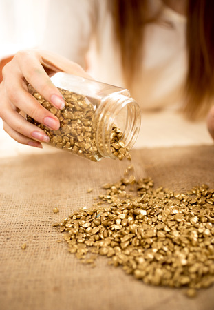 emptying: Closeup photo of woman emptying bullion with gold on burlap