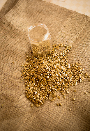 washed out: Pile of washed out gold nuggets and glass jar on burlap