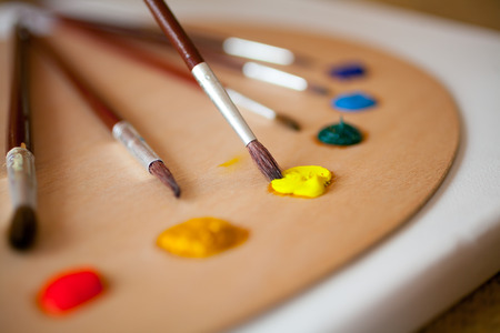 paintbrush: Colorful acrylic paints on wooden pallet. Focus on paintbrush dipped in yellow paint