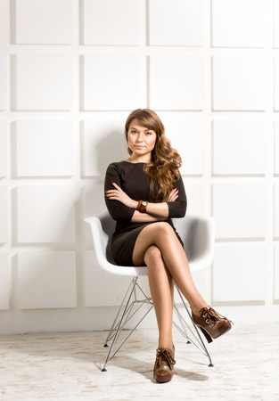 sexy office girl: Beautiful elegant woman in black dress posing in white chair at studio