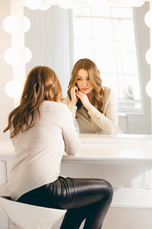 Young stylish woman looking in her reflection at mirror with bulbs