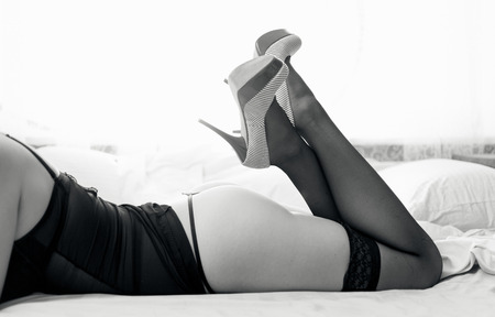 mujer desnuda de espalda: Foto blanco y negro de una mujer desnuda sexy en medias y tacones altos en la cama