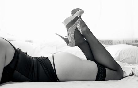 naked young woman: Photo en noir et blanc de sexy femme nue en bas et talons hauts sur lit Banque d'images