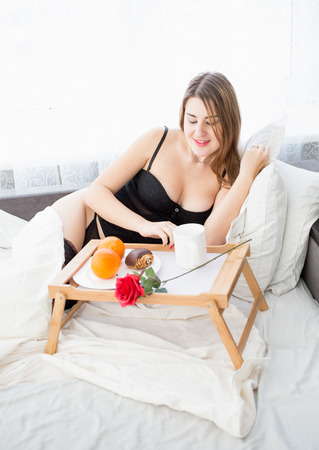 early 30s: Portrait of beautiful woman having breakfast at bed Stock Photo