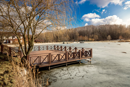 Beautiful wooden pier on lake covered by ice at sunny day photo
