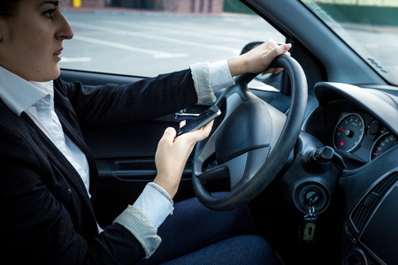 working accident: Closeup photo of young woman driving a car and typing message Stock Photo
