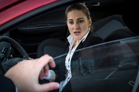 Burglar threatens young  businesswoman sitting in car