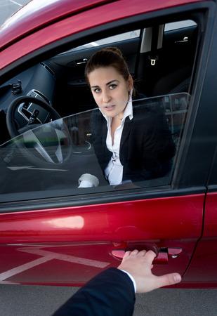 Burglar trying to break into the car. Scared woman blocking the door photo