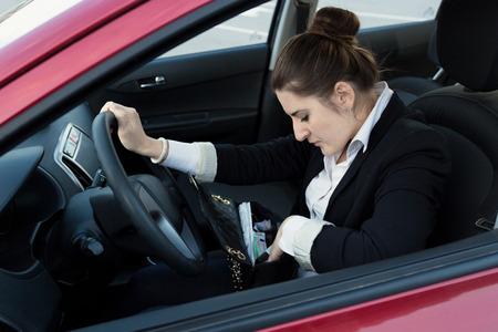 looking inside: Portrait of elegant woman driving car and looking inside handbag