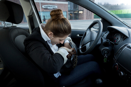 Portrait of young businesswoman sitting on drivers seat and looking inside handbag