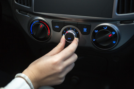 car: Woman turning on car air conditioning system