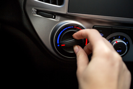 condition: Closeup photo of young woman turning car air conditioner switch