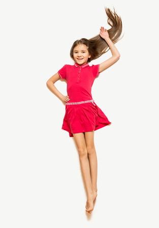 preteens: Isolated photo of cute girl in red dress with long hair lying on floor