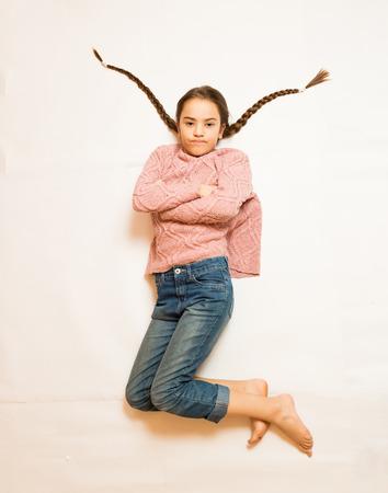 Isolated shot of sad girl with long braids lying on floor photo