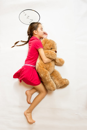 Conceptual shot from top view of cute dreaming girl lying on big teddy bear photo