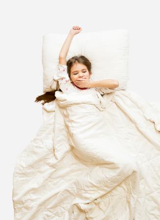 jolie petite fille: Coup isol� de jolie fille b�illant dans le lit au matin