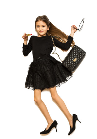 costume jewelry: Isolated photo from high point view of cute girl wearing mothers clothes and shoes