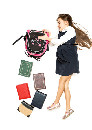 emptying: Conceptual isolated photo of cute schoolgirl emptying backpack full of books