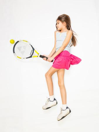 Little girl lying on floor and pretending to play tennis