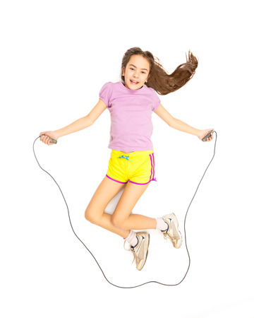 Isolated photo of cute active girl jumping with skipping rope Standard-Bild