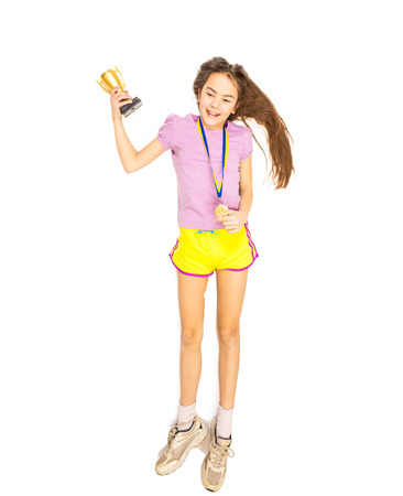 Happy smiling girl posing with cup and gold medal. Isolated shot on floor. photo