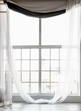 Beautiful high window from ceiling to floor with long white curtains