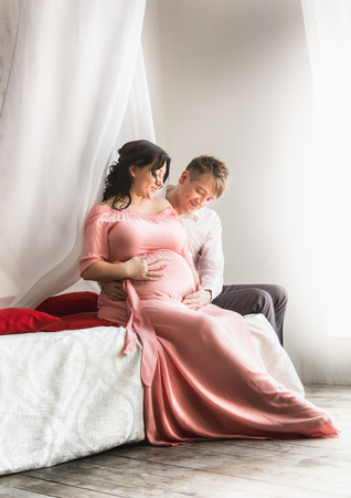 Toned photo of beautiful pregnant couple sitting on bed with baldachin next to window photo
