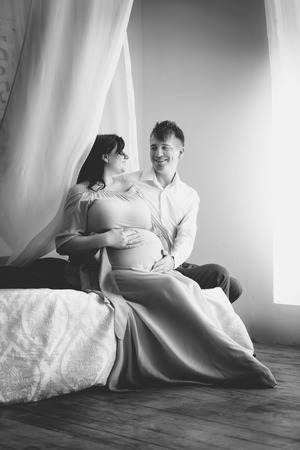 Black and white photo of happy elegant pregnant couple relaxing on luxurious bed photo
