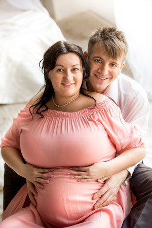 one family: Portrait of handsome man hugging chubby pregnant wife from back