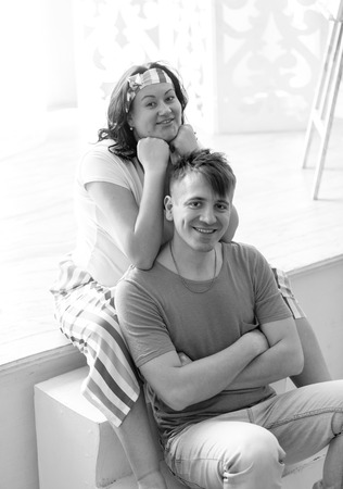 Black and white portrait of happy pregnant woman hugging husband from back Stock Photo